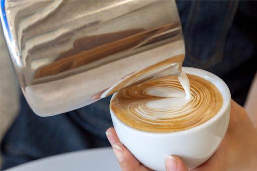 Vierte la espuma de leche en el café haciendo un zigzag para hacer el dibujo.